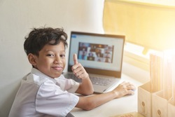 A Malaysian school boy giving a thumbs up during his online class. New normal online classroom for pupil during Covid 19 pandemic. Selective focus with shallow DOF
