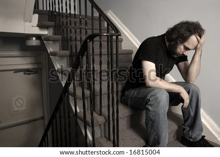 A male adult with overwhelming depression sitting in the stairwell of his apartment building.  Desaturated.