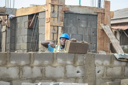 A MALE African construction worker using a Trowel to build a fence on a building site and he is wearing a blue protective helmet and a green reflective traffic jacket to earn a living