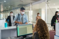 A male airline passenger with mask is handing over his passport at the airline counter check in through an acrylic barrier for disease prevention coronavirus or covid-19 at airport for New normal