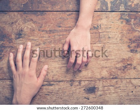A male and a female hand on a wooden table