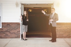 A male and female church members standing at the church doors