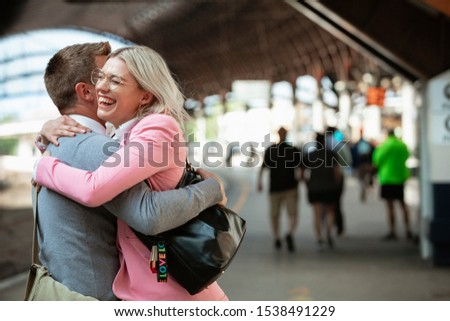A male and female co-worker parting ways after work. They are hugging each other goodbye while laughing.