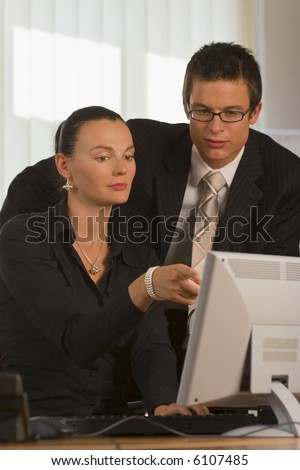 A male and female office worker looking together at a computer monitor