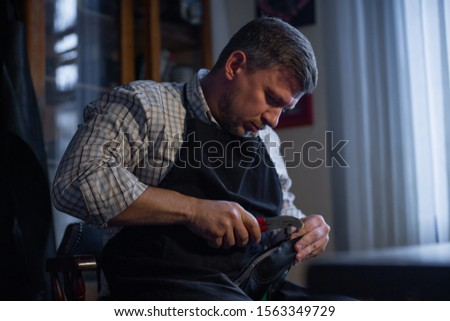 A male artisan in a work apron sits at a table and makes a workpiece with pliers. The process of making handmade shoes