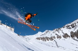 A male athlete skier in an orange trigger makes a jump jump with a grab with flying snow powder against the background of Mount Elbrus in the North Caucasus. Winter Extreme Sports Concept