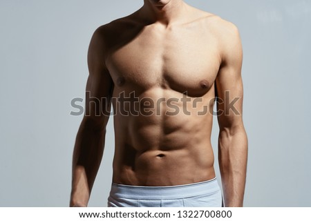 A male athlete with a muscular muscular body is engaged in fitness sports #1322700800