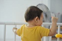 A male baby stands on a shackle against a child.
