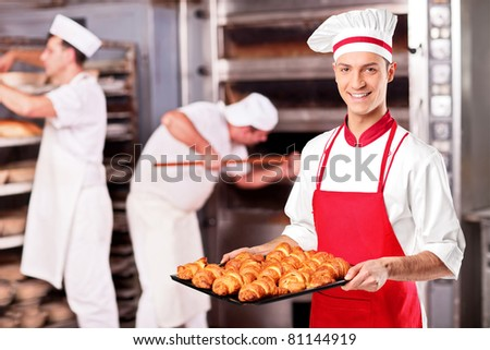 A male baker holding freshly baked croissants in bakery
