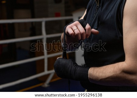 A male boxer in black sportswear reels on the arm a special boxing bandage. Photos for advertising sports or fighting club. High quality photo Foto stock ©