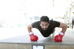 A male boxing athlete is exercising before returning to practice in the gym without removing the glove.