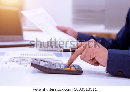 A male business man sits a long time earning money from doing business using a calculator for long words. Stock photo ©