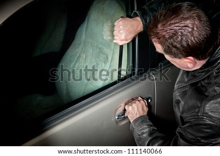 A male car thief uses a flat metal lock pick to break into a vehicle.