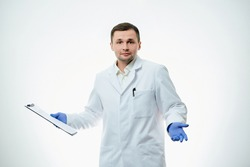 A male caucasian doctor in a white lab coat and blue disposable medical gloves is surprised with a helpless gesture. A scientist is isolated over white background.