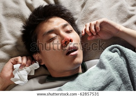 A male Chinese man is sleeping while catching cold and breathing through mouth because of the flu
