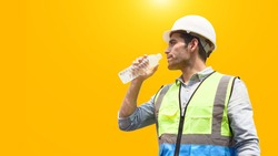 A Male construction worker or handsome engineer in protective clothing and a helmet, is drinking water to quench his thirst isolated on yellow background with copy space.
