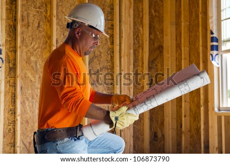 A male construction worker reads blueprints while working at a construction site