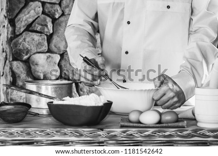 a male cook in a white garment whisk the whisk the batter, selective focus, black white photo #1181542642