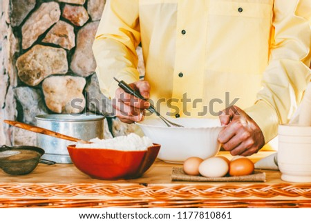 a male cook in a yellow garment whisk the whisk the batter, selective focus #1177810861