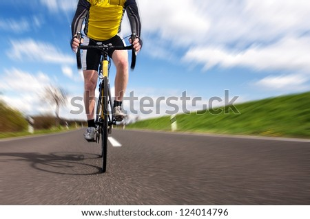 A male cyclist riding a bike uphill along a road; clear summer day
