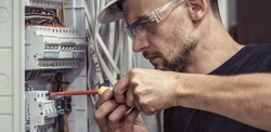 a male electrician works in a switchboard with an electrical connecting cable, connects the equipment with tools, the concept of complex work, space for text