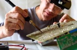 A male engineer repairs an electronic board. Soldering the electronic board.