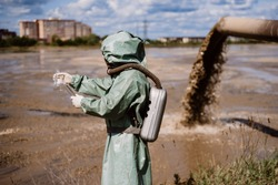 A male environmentalist in a protective suit and gas mask takes a sample of water. Scientist doing toxicological study.