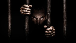 A male face stares to the camera from behind prison bars