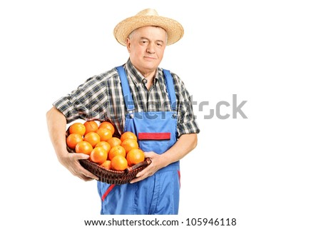 A male farmer holding a basket full of oranges isolated on white background