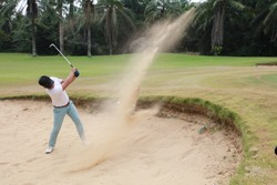 A male golf player hit the gold ball out from Bunker, Close up of man hitting golf shot in a bunker