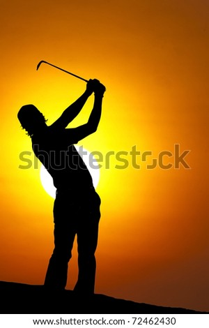 A male golfer enjoys an early round during sunrise.