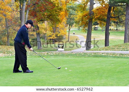 A male golfer plays a game on a beautiful fall day.