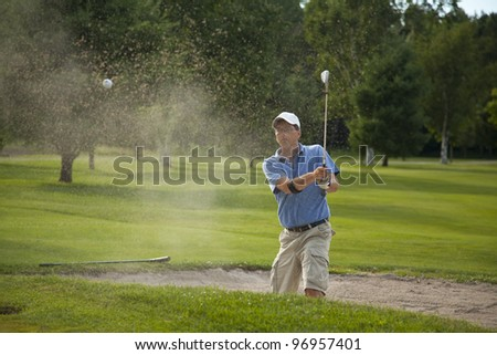 A male golfer takes a swing at his ball in a sand trap and creates a big spray of sand.