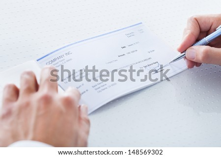 A Male Hand Filling Out The Amount On A Cheque