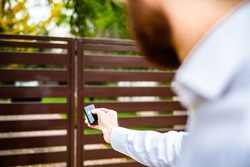 A male hand holding a remote control to open an entrance gate. An automatic opening, closing of a driveway gate. A modern house.