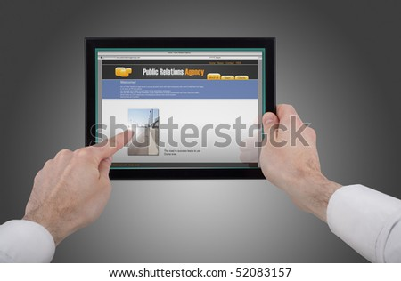 a male hand holding a touchpad pc, one finger touches the screen and surfing the web - stock photo