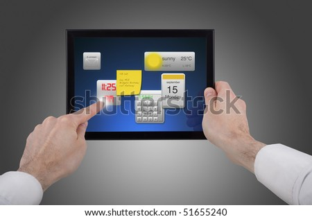 a male hand holding a touchpad pc, one finger touches the screen and uses little programmes