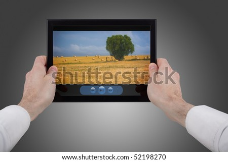 a male hand holding a touchpad pc showing a movie, isolated on white
