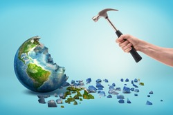 A male hand holds a metal hammer near a semi-broken Earth globe with small pieces fallen out of it. Human vs Earth. Environmental issues. Destroying the Earth.