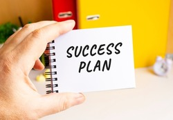 A male hand holds a notepad on a spring with the written SUCCESS PLAN text. Office space. Business concept.