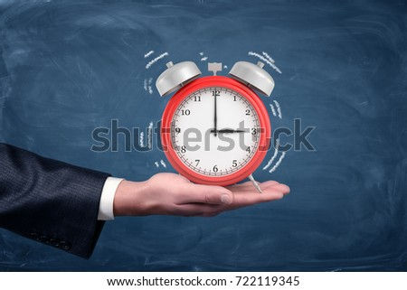 A male hand holds palm up a large red alarm clock with white sound wave lines on blue background. Last time for everything. Final deadline. Wake up call.