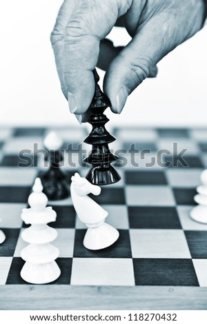 A male hand moving some chess pieces