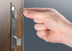 A male hand ready to insert a token into the slot of a vintage chrome coin receptacle mounted on a wooden surface - 3D render