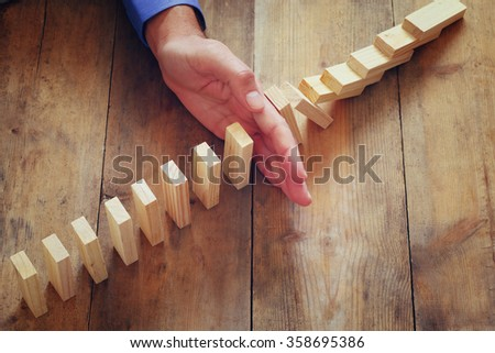 a male hand stoping the domino effect. retro style image executive and risk control concept