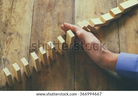 a male hand stopping the domino effect. retro style image executive and risk control concept