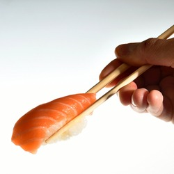 A male hand with a piece of salmon sushi nigiri isolate on white background