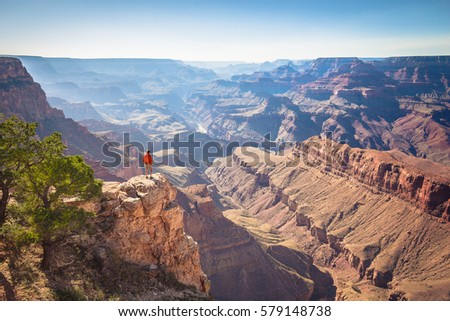 A male hiker is standing on a steep cliff taking in the amazing view over famous Grand Canyon on a beautiful sunny day with blue sky in summer, Grand Canyon National Park, Arizona, USA #579148738