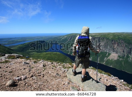 A male hiker on Gros Morne Mountain standing above Ten Mile Pond in Gros Morne National Park, Newfoundland, Canada.