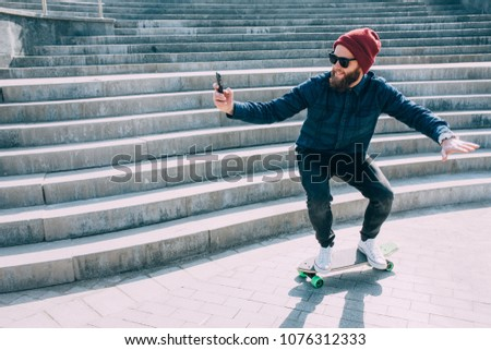 A male hipster rides on a longboard and making Selfie on a smartphone