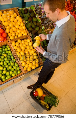 A male in a grocery store buying lemons - sharp focus on lemons